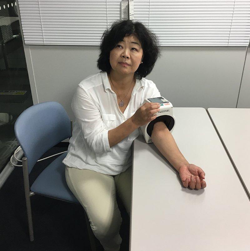 おそるおそる血圧計を測るオバ記者