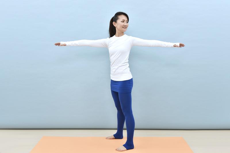 脚を肩幅に広げて、両手を横にまっすぐ突き出す