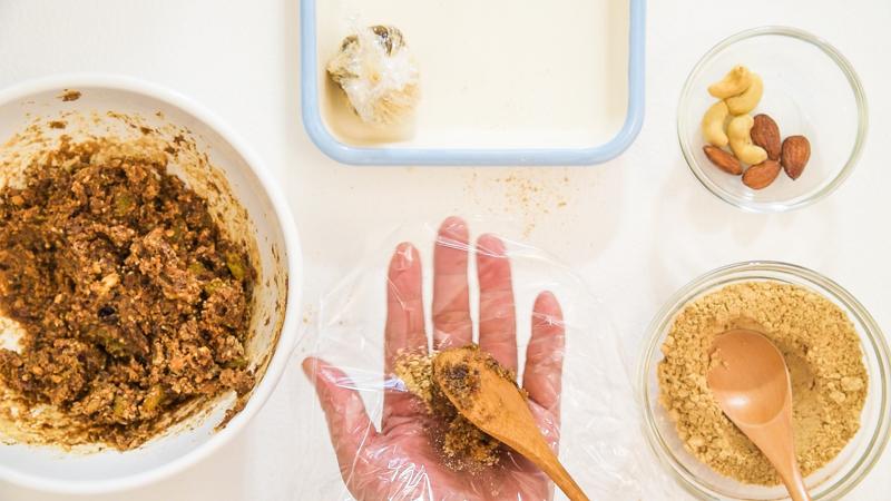 手のひらにラップをのせ、材料を丸めるところ