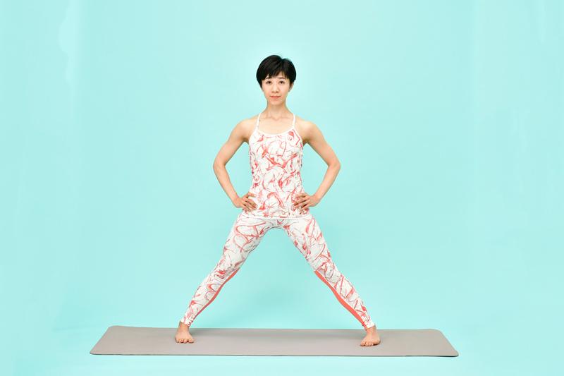 両脚を左右に大きく開いて立つ女性
