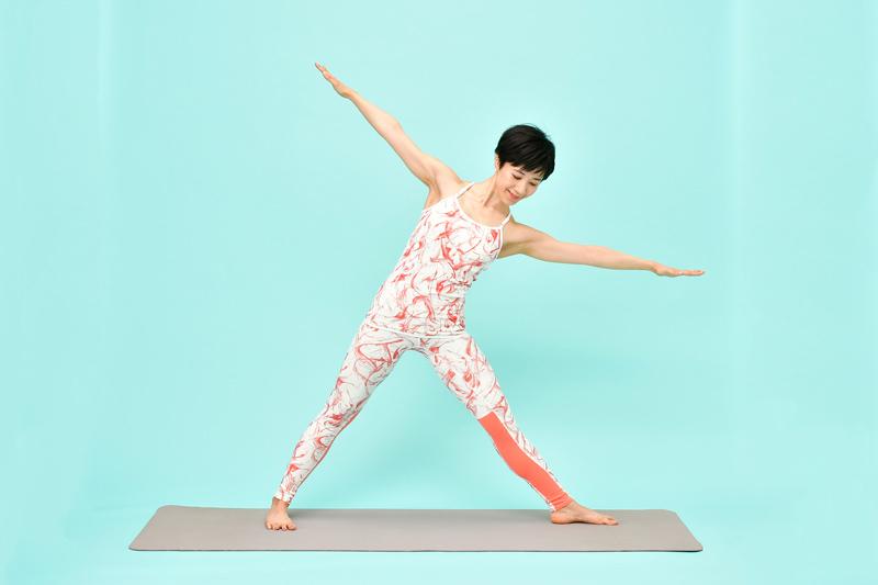 息を吸いながら、両腕を肩のラインに長く伸ばす女性