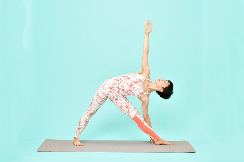 息を吸いながら、背骨を伸ばすように引き上げる女性