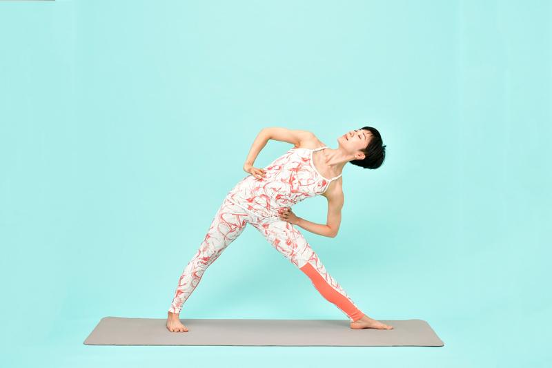 腰に両手を当てて、息を吸いながら、ゆっくりと上半身を起こす女性