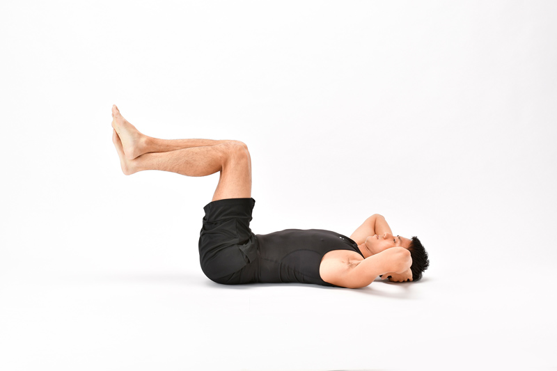仰向けになった状態で、両脚を引き上げている男性