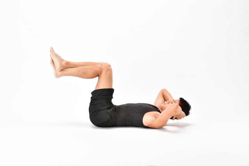 仰向けになった状態で、頭を少し上げ両脚を引き上げている男性