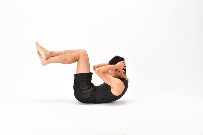 仰向けになった状態で、両脚を引き上げて腹筋をする男性