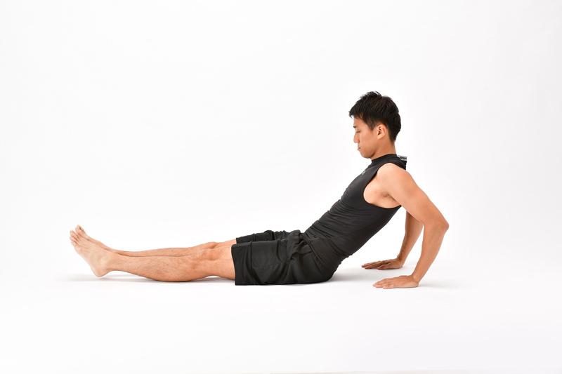 床に脚を伸ばして座り、両手を体の後ろに置く男性