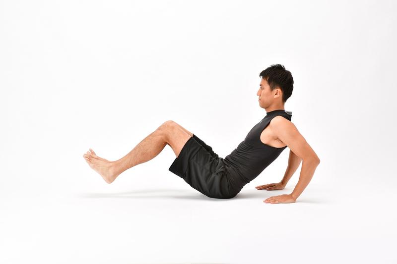 床に脚を伸ばして宙に浮かせ、両手を体の後ろに置く男性