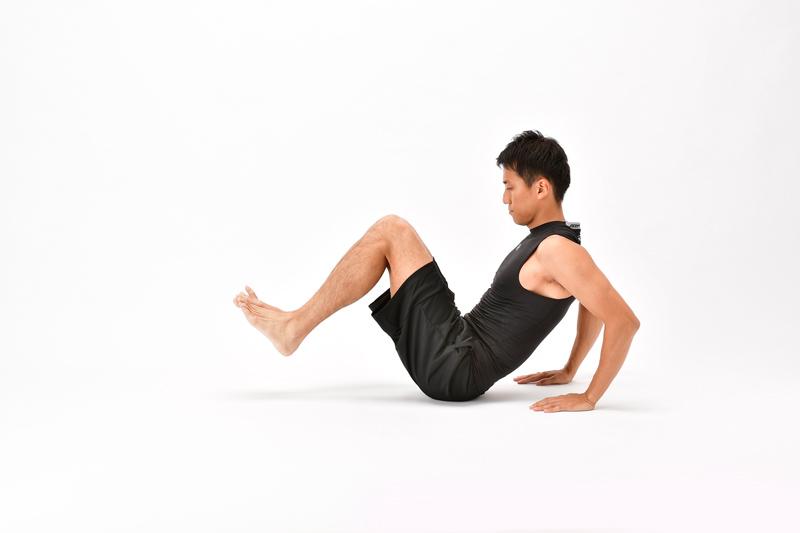 座った状態で両膝を体に近づけ、両手を体の後ろに置く男性