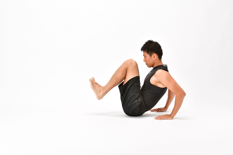 座った状態で両膝を体にさらに近づけ、両手を体の後ろに置く男性