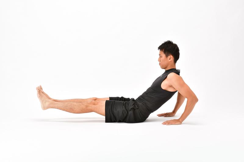 座った状態で両脚を伸ばして宙に浮いた状態で、両手を体の後ろに置く男性