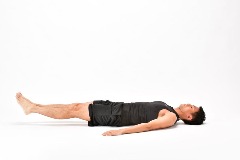 仰向けになった男性が、両脚を揃えたまま、床ギリギリまで下ろす
