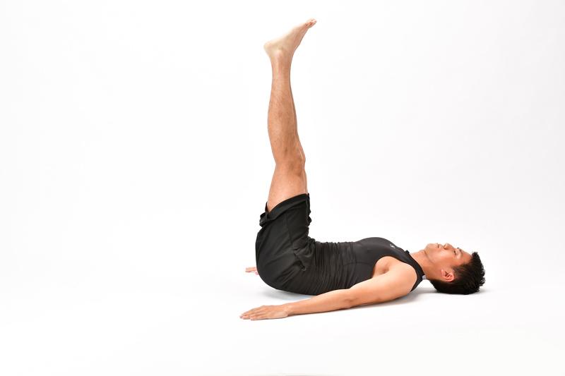 仰向けになった男性が、両脚を揃えたまま、90度に持ち上げていく