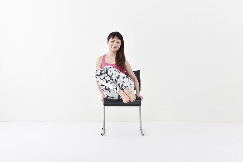 両膝をくっつけたまま脚を右側に持ち上げている女性