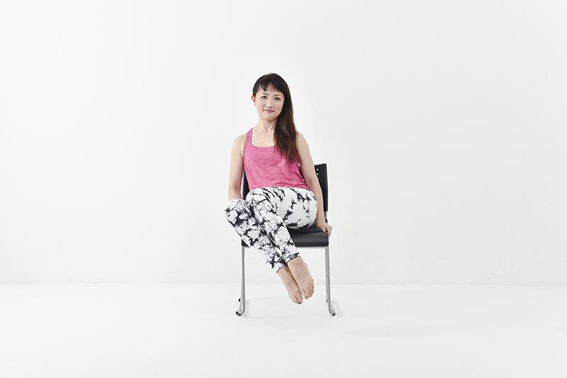 両膝をくっつけたまま脚をやや高めに右側に持ち上げている女性