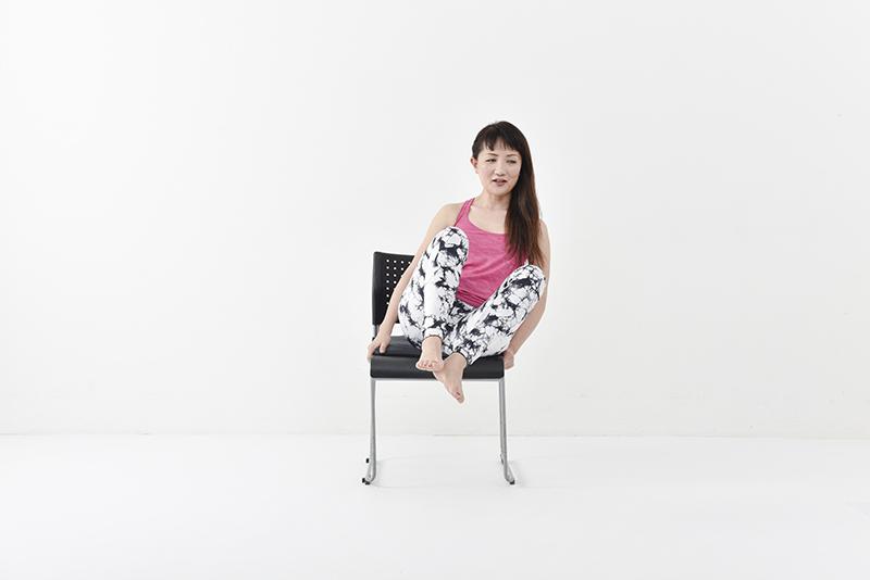 椅子に座って、両足をあげているが両膝が離れてしまっている女性