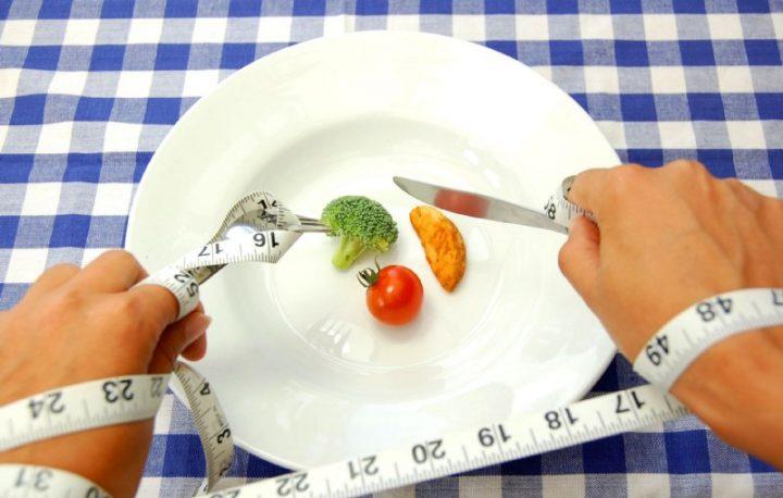 皿にのった少ないおかずをナイフとフォークで食べようとしている