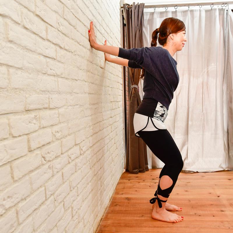 両手を壁について両膝を曲げている和田清香さん