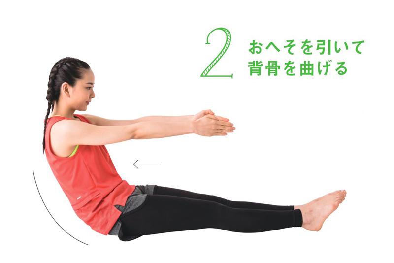 床に座って、両手と両膝が平行になるようにまっすぐ伸ばし、おへそを引く女性