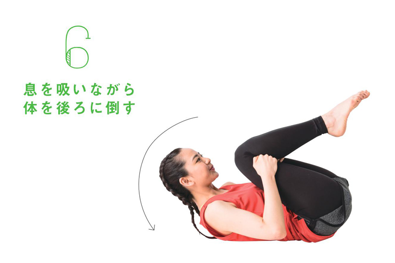 床に座った女性が、体を後ろに倒している