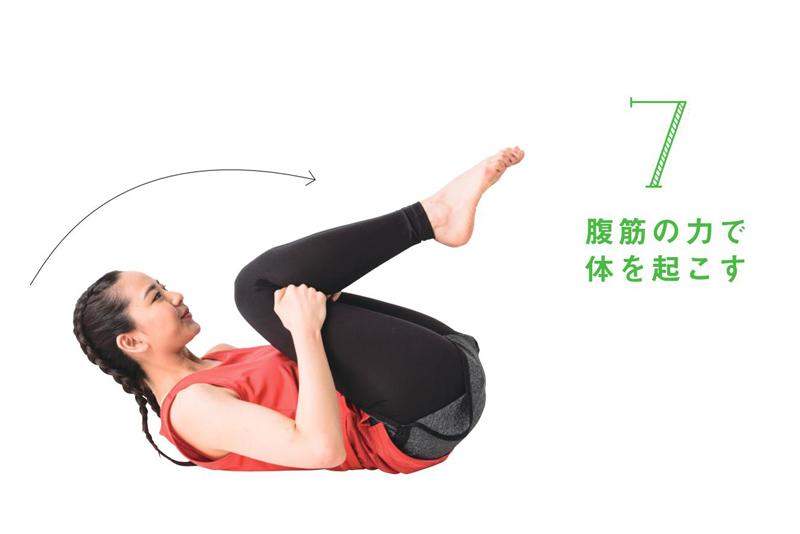 腹筋の力で起き上がり、両足が浮いたところでキープしている女性