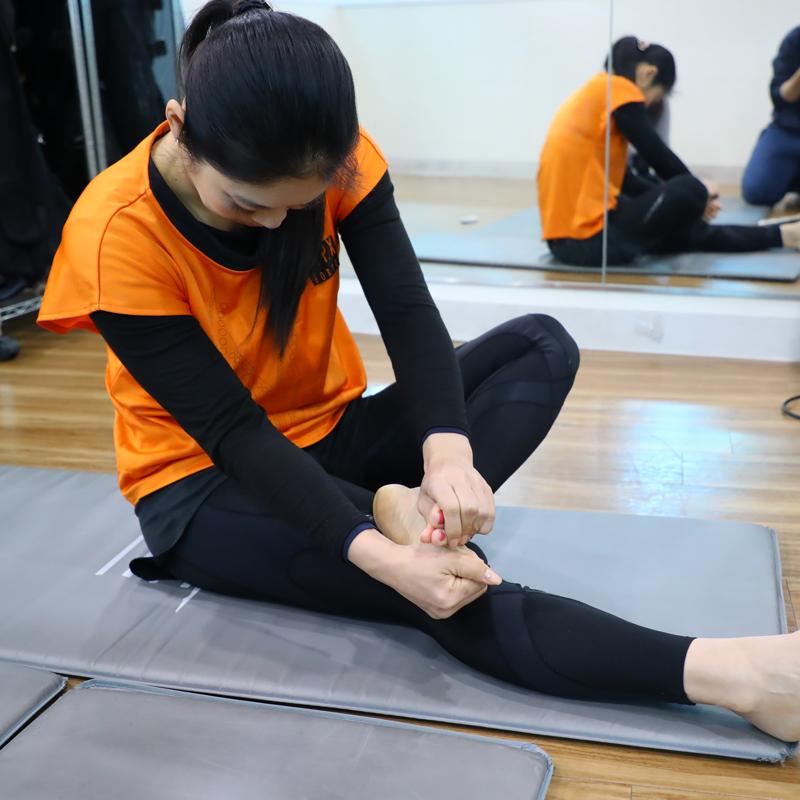 両手で片方の足の指を持ち、指を上下に分けるように動かす女性
