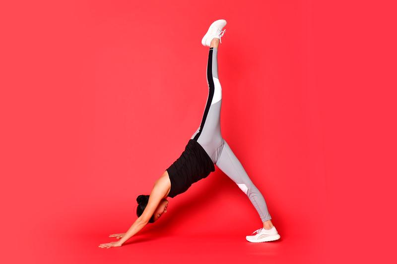 両手を床につけた状態で、左脚を天井方向へ蹴り上げている女性