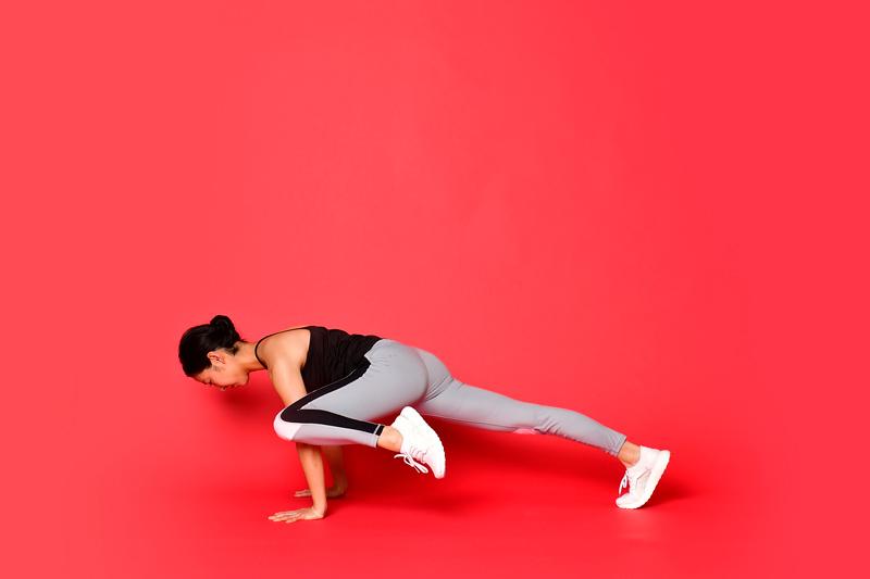 両手を床につけた状態で、左ひざを左ひじの外側につける女性
