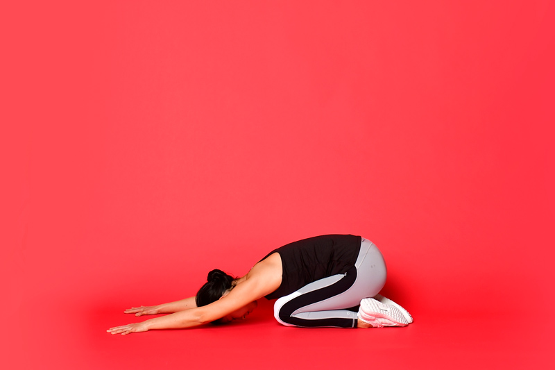 両足をつけた正座の状態で、両手を伸ばしている女性