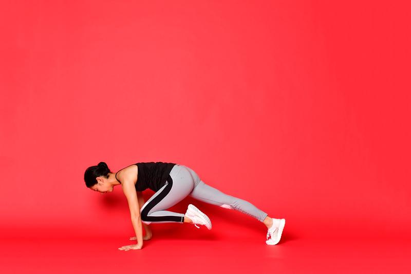 両手を床につけた状態で、左ひざを左ひじの中央につける女性