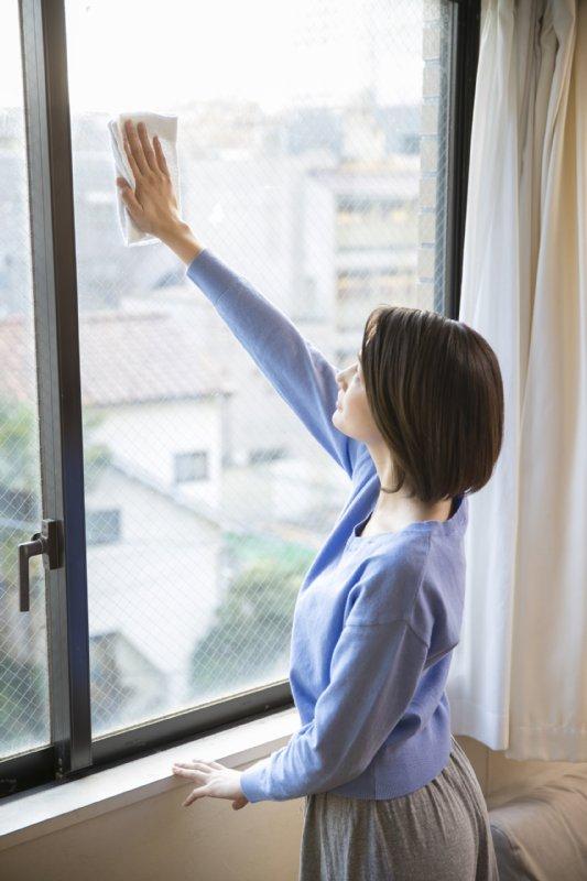ひじを伸ばしたまま窓拭きをする女性