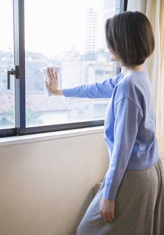 窓の低い位置を、ひじを伸ばしたままで拭く女性