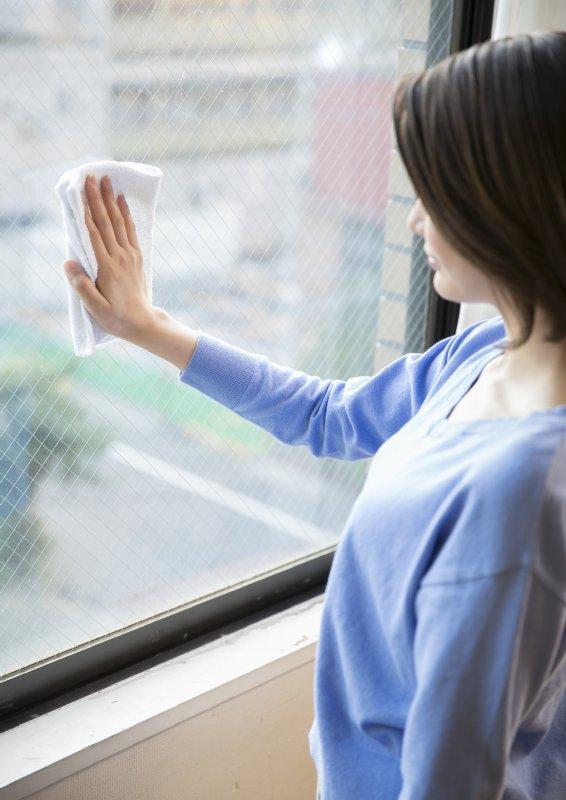 肘が曲がった状態で窓を拭く女性