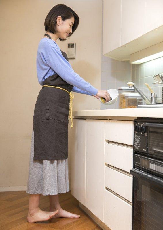 洗い物時に後ろ足のつま先を上げてキープしている女性