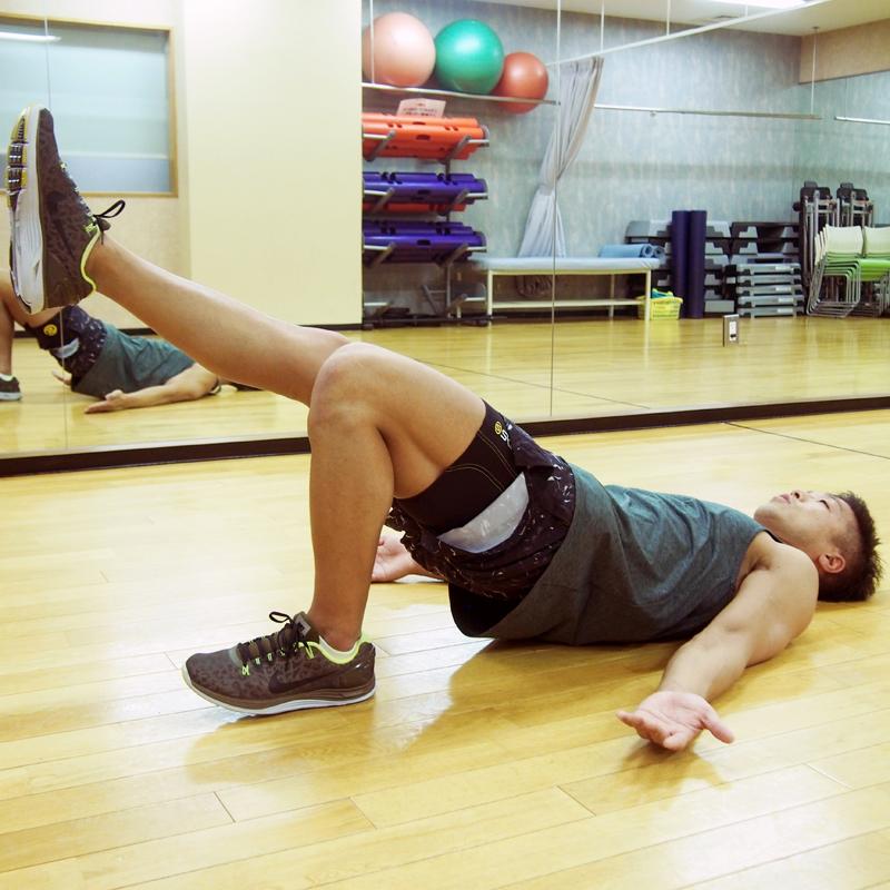 仰向けになる膝を曲げた状態から腰を浮か、右足をまっすぐ上げる大沼友和さん