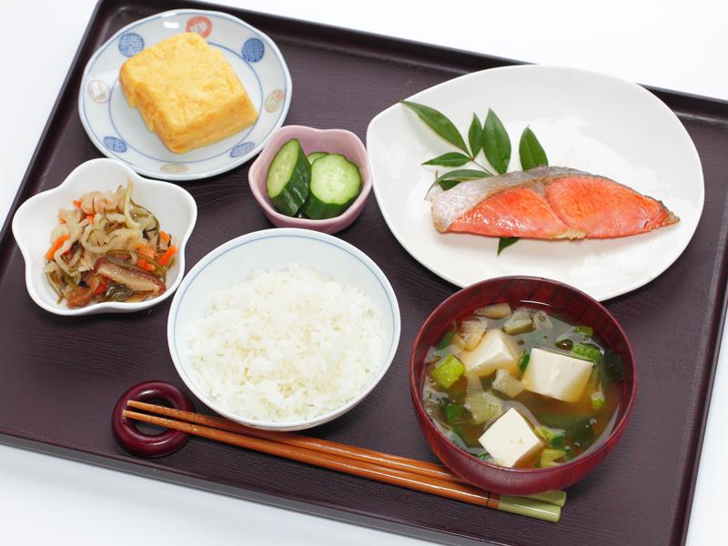 ご飯、みそ汁、卵焼き、漬物、焼鮭などが並んだ食事