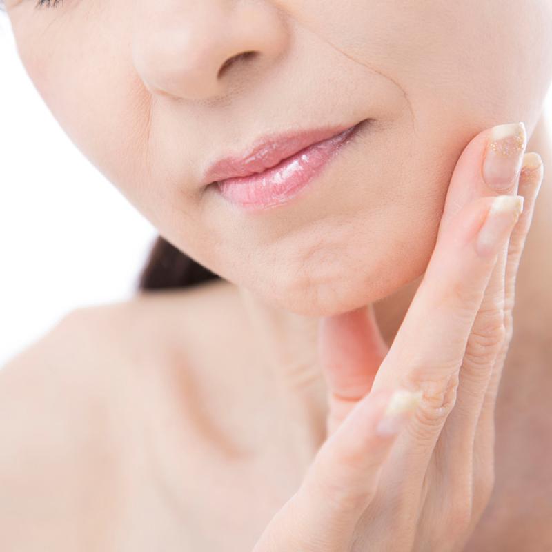 老化を気にしてる顔の肌を触る女性