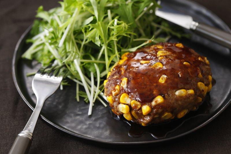 お皿に乗ったコーンと豚の照り焼きバーグ。野菜も添えられている