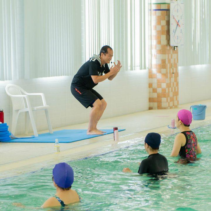 プールサイドで中腰になるインストラクターの宮田健右さんとプールに入っている水着の女性3人