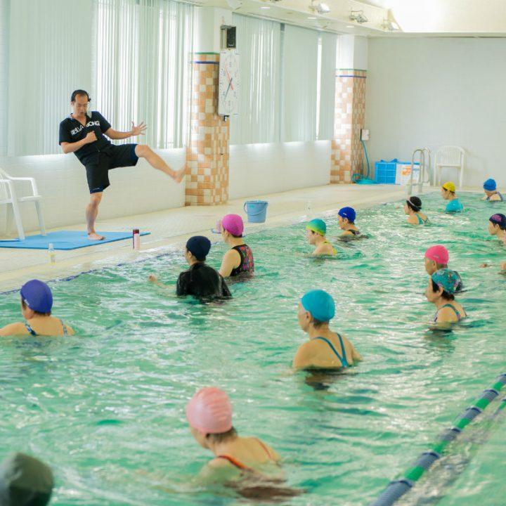 プールサイドでキックをレクチャーするインストラクターの宮田健右さんとプールの中にはそれを真似する水着姿の女性たち