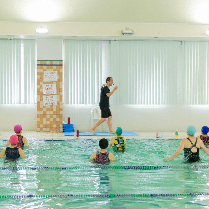 プールサイドを歩くインストラクターの宮田健右さんと水着でプールに入っている6人の女性