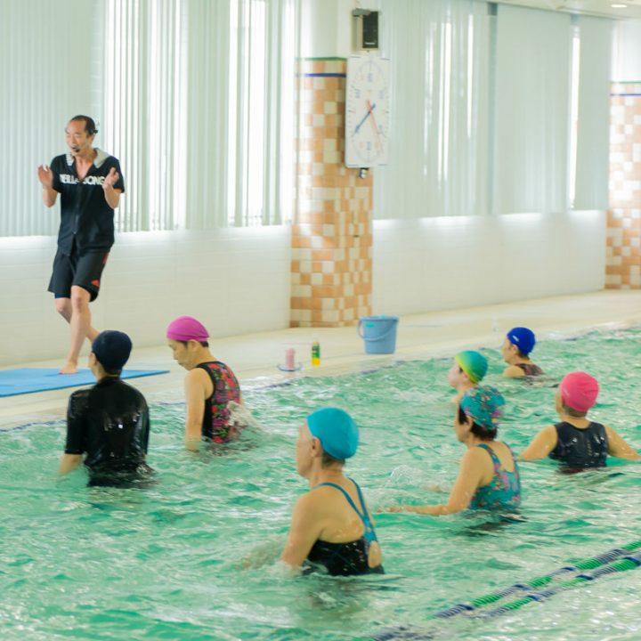 プールサイドで手拍子するインストラクターの宮田健右さんとプールの中でジャンプする水着姿の女性たち