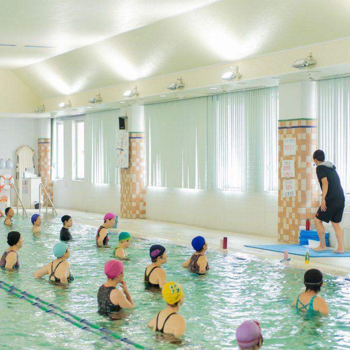 プールサイドで説明をするインストラクターの宮田健右さんとプールに入っている水着の女性たち