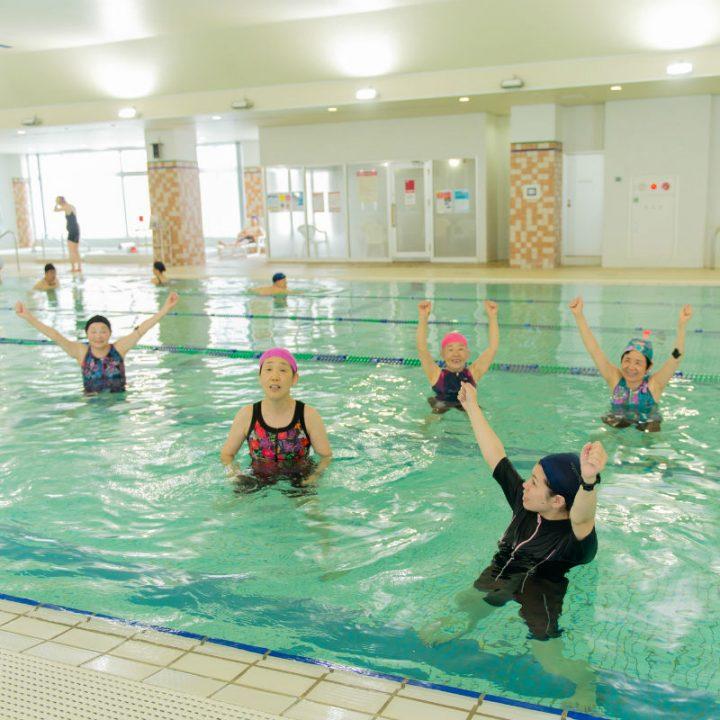 プールの中で両手を挙げる水着姿の女性たち