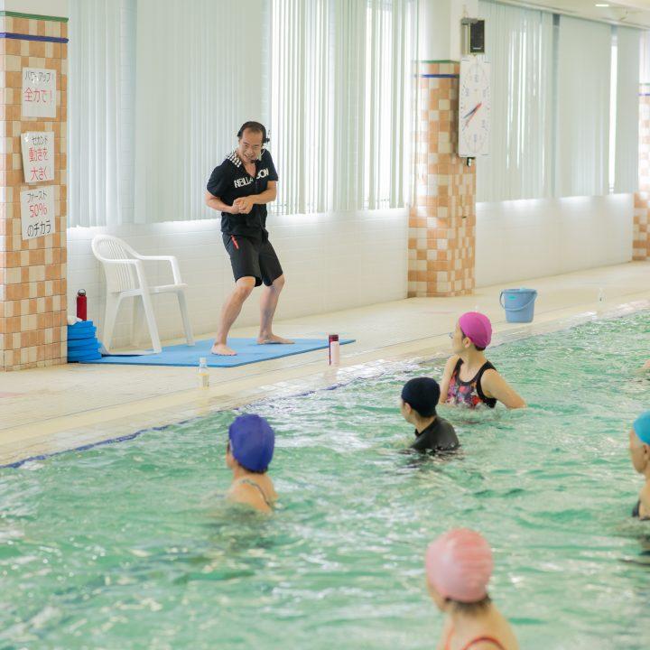プールサイドで肘打ちの動きをするインストラクターの宮田健右さんとプールの中に動きをまねする水着姿の女性たち