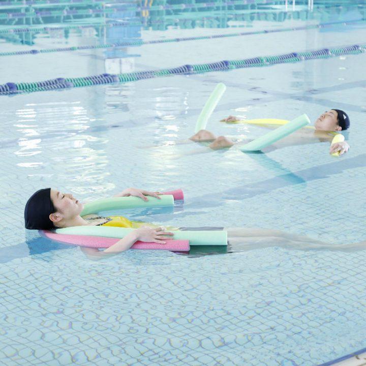 棒状のものを用いてプールに浮く男女