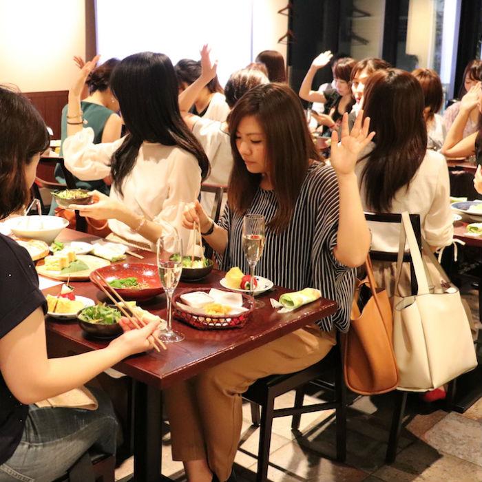 食事をしながら手を挙げる女性たち