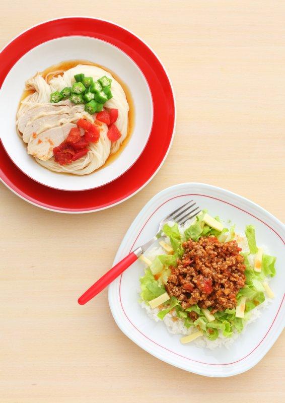 お皿に盛り付けられた、蒸し鶏のせそうめんとマイルドなタコライスの2皿