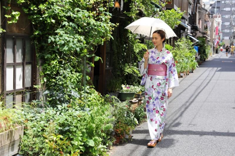 浴衣を着た女性が日傘を差して歩いている