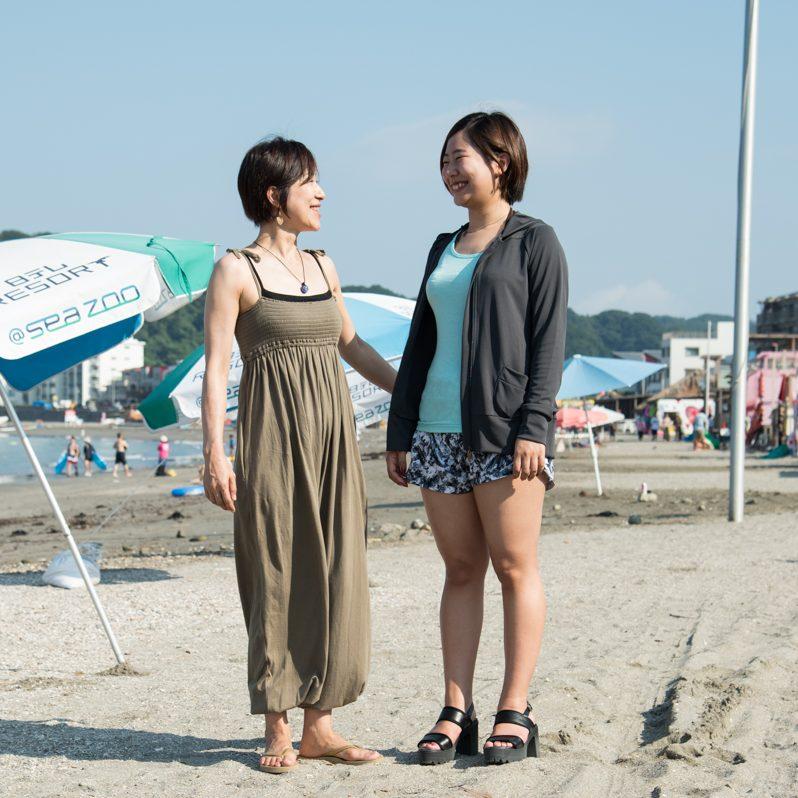 ビーチで向き合って話をする津下恵子さん、佐藤みのりさんの全身